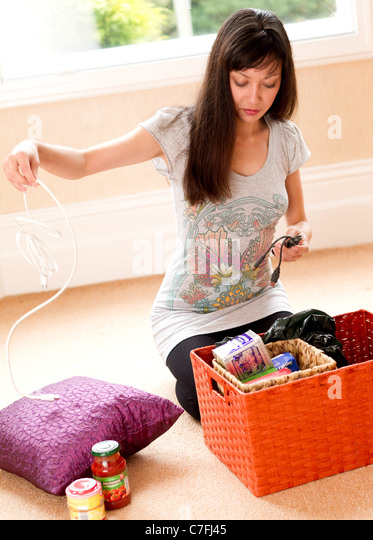 Girl unpacking box of goods - Stock Image