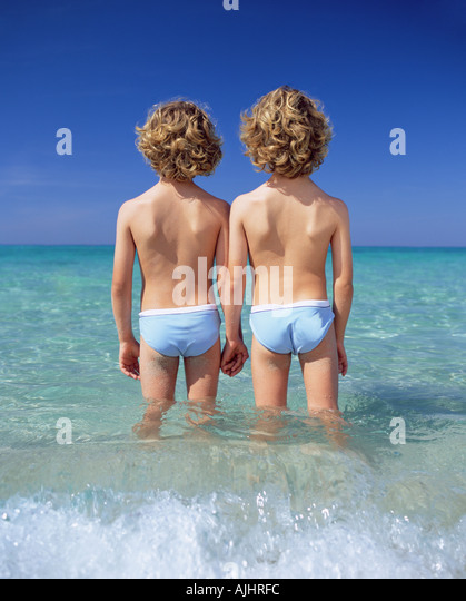 Twin boys standing in the sea - Stock Image