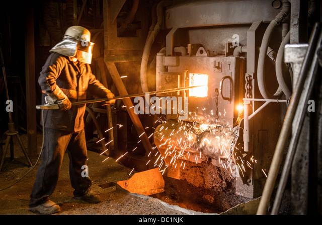 Steel worker in front of furnace in steel foundry - Stock Image