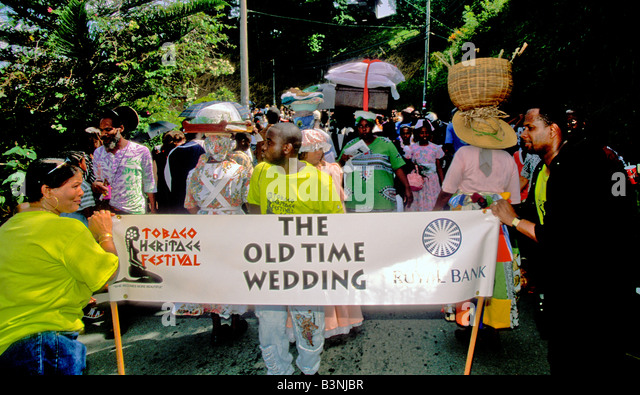 Wedding party holds banner marching the streets of Moriah village old time wedding at Tobago Heritage Festival ole - Stock Image
