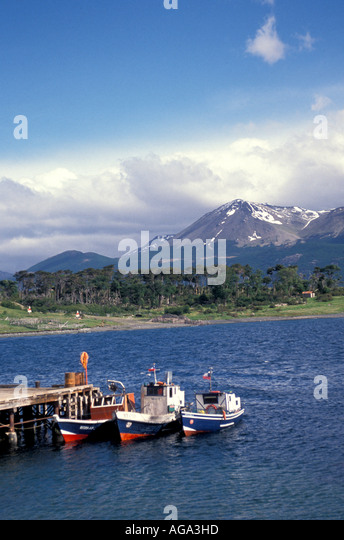 Chile South America Punta Arenas fishing boats snow-capped mountains in background - Stock Image