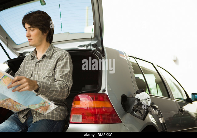 At gas station refueling, checking map - Stock Image