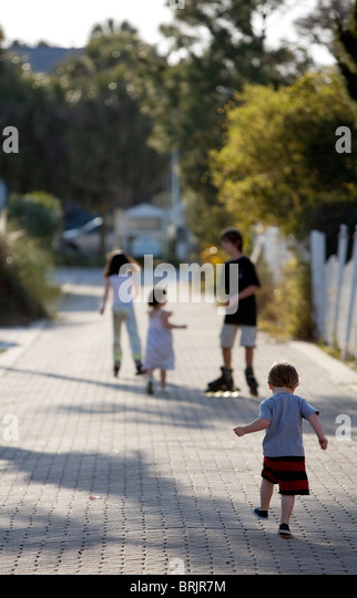 A group of kids are roller blading and walking down an alley. - Stock Image