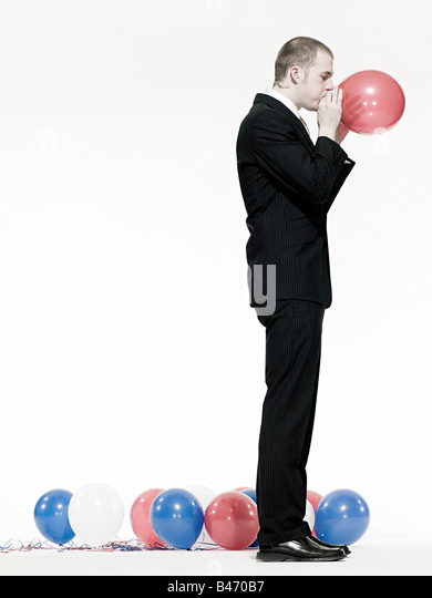 Man blowing up balloon - Stock Image
