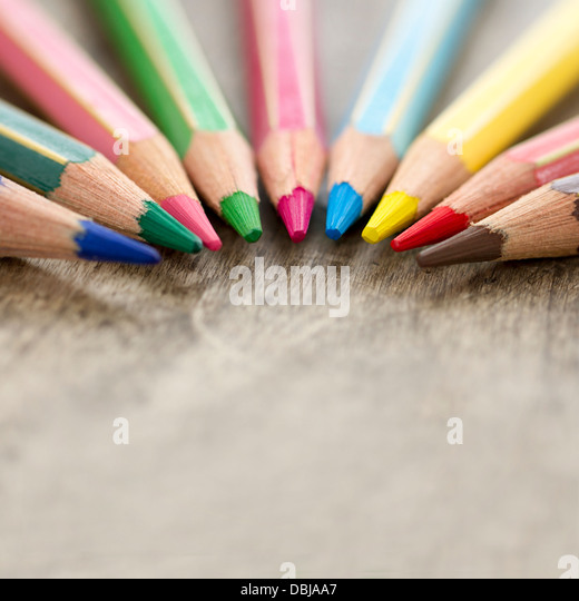 Macro closeup of colorful wooden color pencils on rustic background and selective focus and copy space - back to - Stock Image
