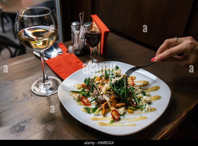 Woman eats healthy tasty salad with beef tongue, and arugula sauce. Hand are holding fork over the dish. - Stock Image