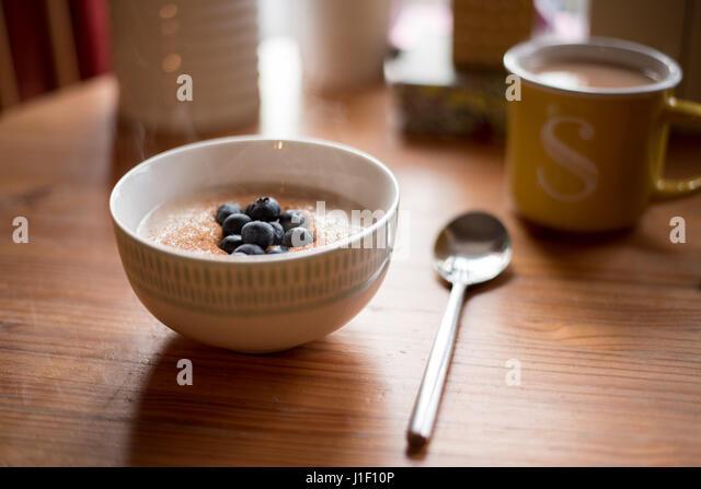 Steaming bowl of porridge in breakfast table scene with mug of tea. - Stock Image