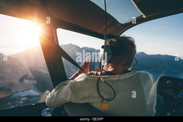 Rear view of female tourist on helicopter tour taking pictures while flying over mountains on a sunny day. - Stock Image
