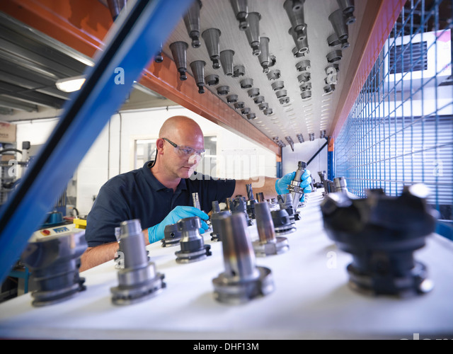 Engineer selecting lathe cutting tools in factory - Stock Image