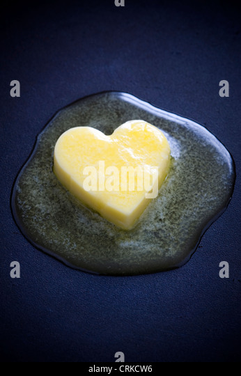 a heart shaped butter pat melting on a non-stick surface representing a healthy heart concept - Stock-Bilder