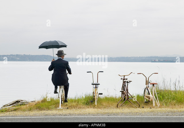 Businessman with row of stationary bikes - Stock Image