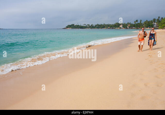 TOURISTS WALKING ON UNAWATUNA BEACH - Stock Image