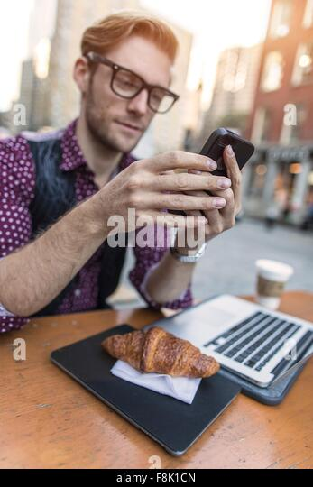 Young businessman having working lunch at sidewalk cafe, New York, USA - Stock Image