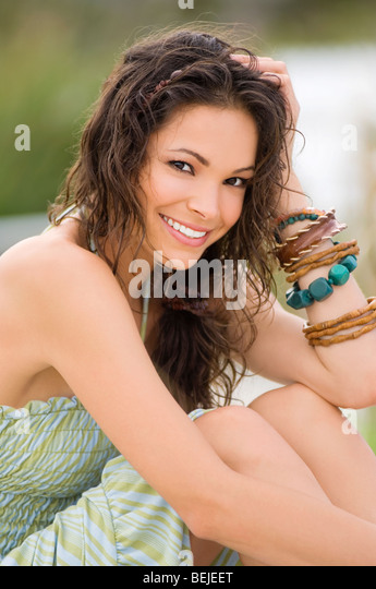 Portrait of a young woman sitting on the beach and smiling - Stock-Bilder