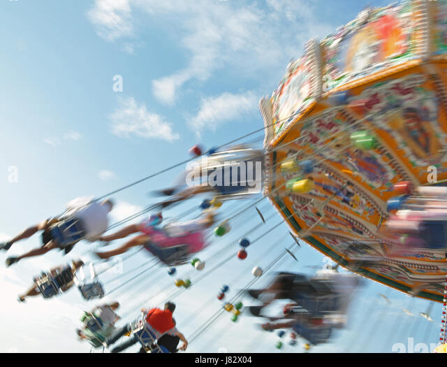 fair carousel decent honourable speed velocity humans human beings people folk - Stock Image