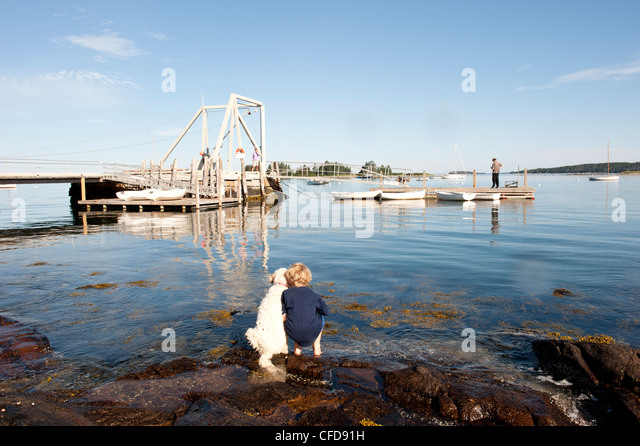a boy and his dog watch a fisherman  fishing from the dock - Stock Image