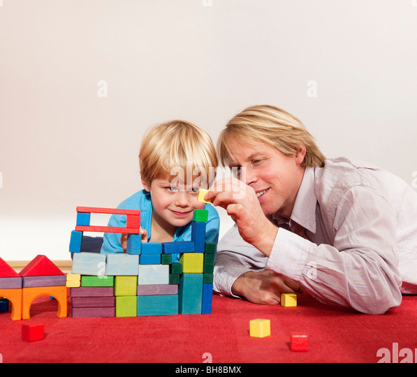 father and son play with building blocks - Stock Image