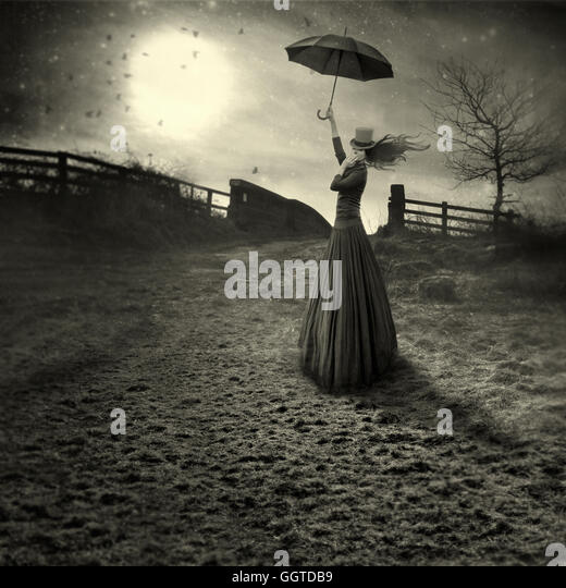 young woman like marry Poppins  with umbrella standing in fields - Stock Image