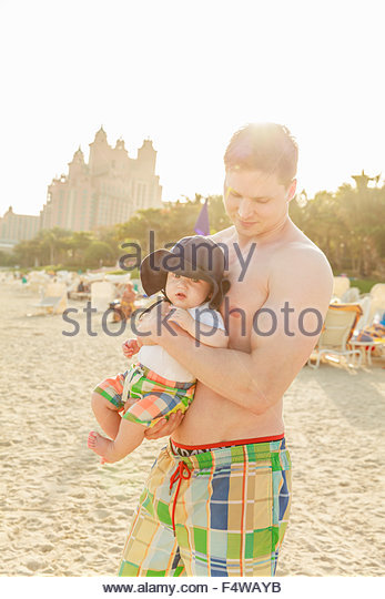 Man holding son (12-17 months) on beach - Stock Image