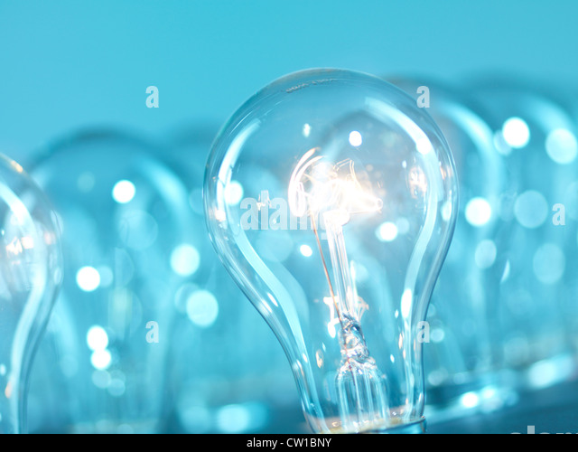 One lit incandescent tungsten light bulbs out of many. Abstract blue background. - Stock Image