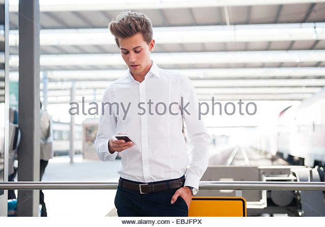 Young businessman holding smartphone - Stock-Bilder
