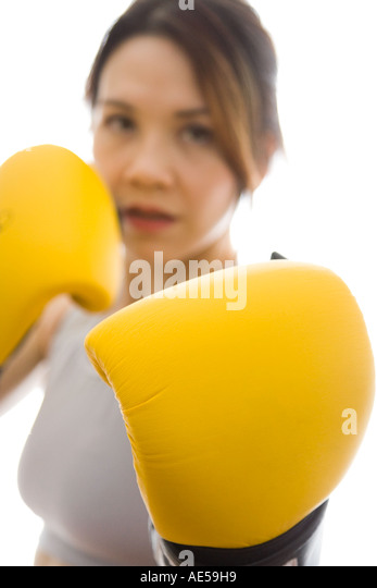 Attractive woman wearing boxing gloves ready to fight with glove in foreground - Stock Image