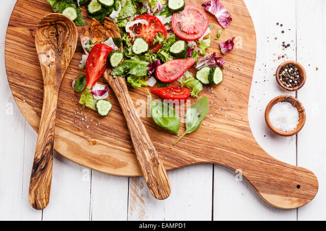 Ingredients of Fresh vegetable salad on olive wood cutting board - Stock Image