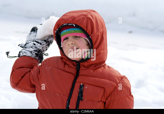 Girl age  7 attempting to throw snowball winter in a city park. St Paul Minnesota MN USA - Stock Image
