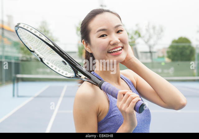 Portrait of young female tennis player on tennis court - Stock Image