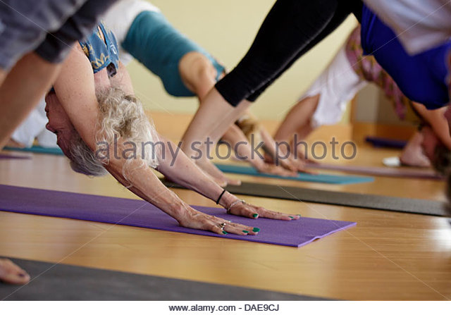 Group of mixed age women practicing yoga - Stock Image