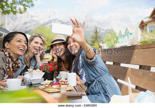 Women taking cell phone picture at cafe - Stock Image