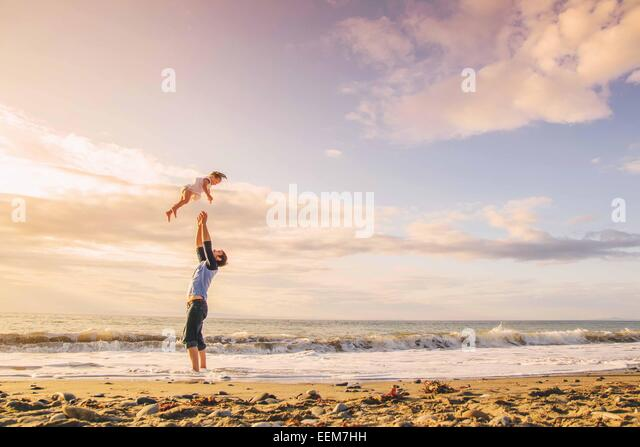 Father throwing young girl (2-3) in to air on beach - Stock Image