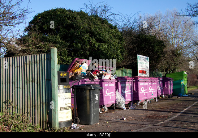 Overflowing recycling bins filled with the wrong rubbish.  Bins marked mixed glass only are filled with cardboard - Stock Image