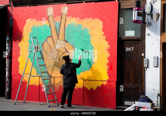Artist painting a large graffiti for Notting Hill Carnival in Portobello Road, London, UK - Stock Image