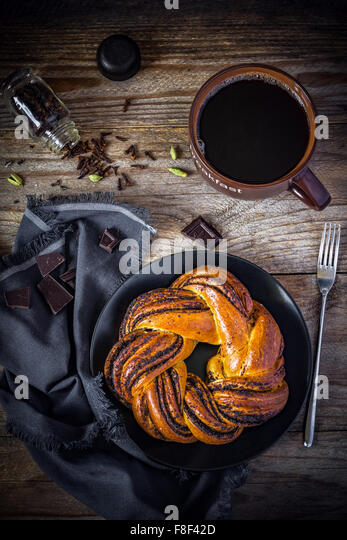 Sweet pastry and cup of black coffee on vintage wooden table, top view - Stock Image