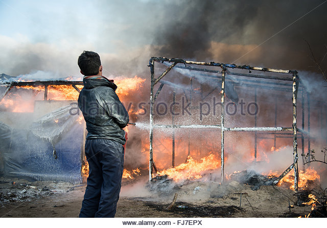 Calais, France. February 29th, 2016. A man extinguishes flames set by just-evicted refugees at the 'Jungle' - Stock Image