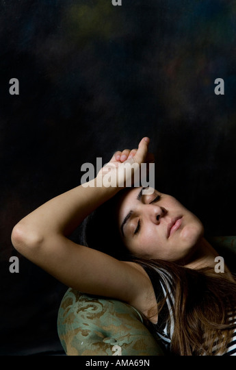 Sad woman laying on a sofa in the dark - Stock Image