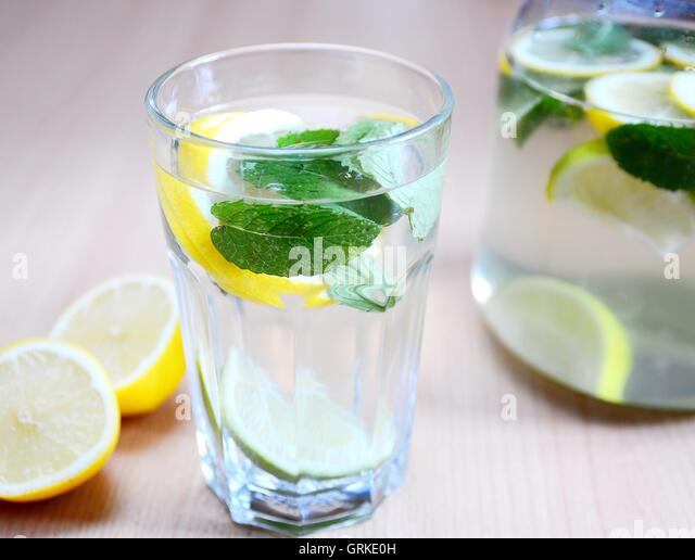 Fresh non-alcoholic drink with water, mint leaves, peaces of lemons and limes in glass. - Stock Image