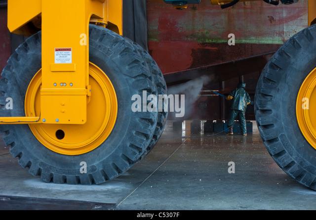 Looking past large tires on a Marine Travelift, a crew member washes boat hull, Kodiak Boat yard, Alaska - Stock Image
