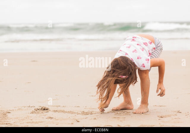 Girl (4-5) drawing in sand - Stock-Bilder