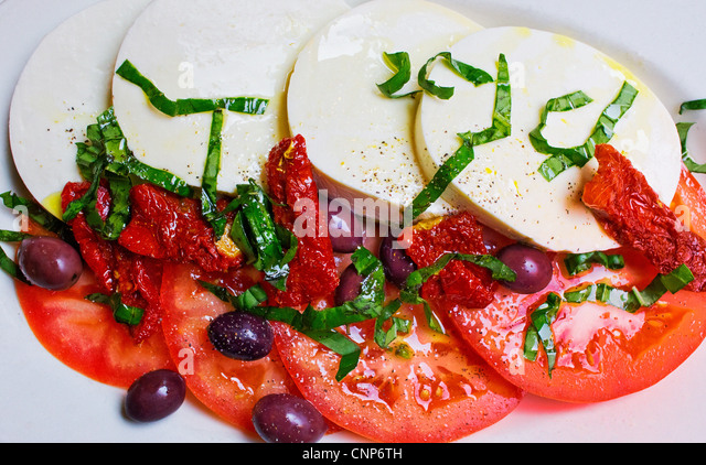 Caprese salad with mozzarella, tomatoes, basil, olives, olive oil. Stock Photo