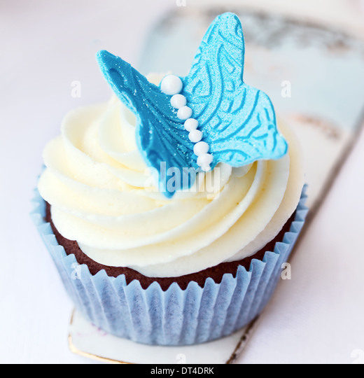 Cupcake decorated with a blue sugar butterfly - Stock Image