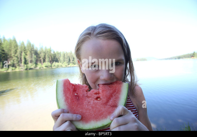 girl eating a slice of watermelon on summer day - Stock Image