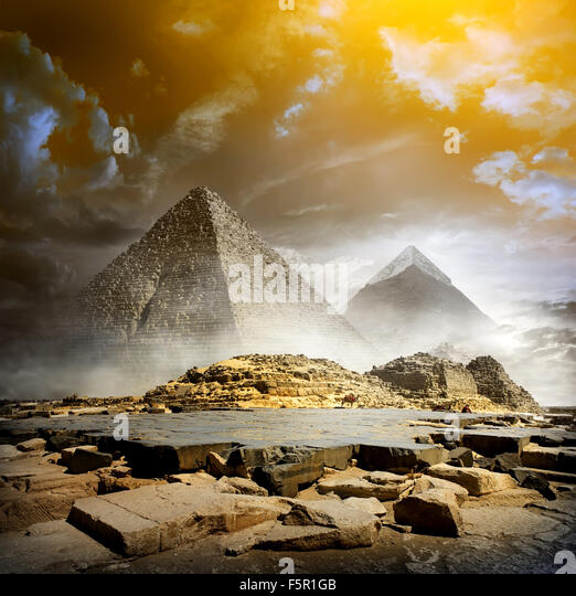 Orange storm clouds and fog over egyptian pyramids - Stock Image