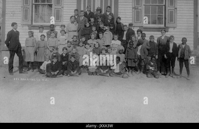Full length landscape shot of schoolchildren, some seated, some standing, some African American, outdoors; Haleyville, - Stock Image