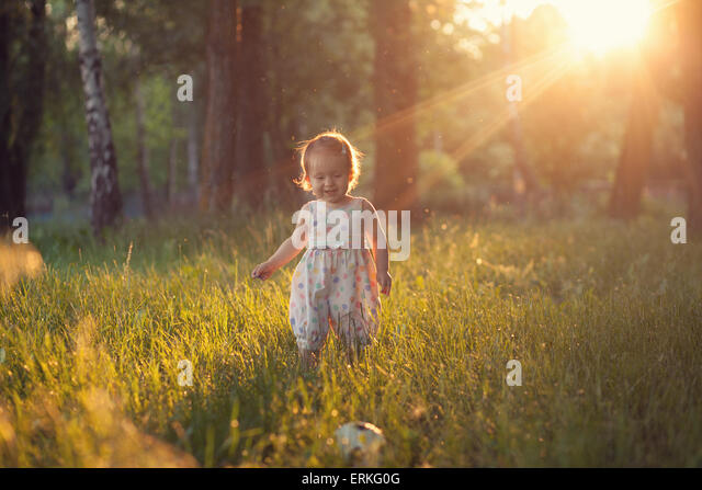 Playing baby in sunset lights - Stock Image