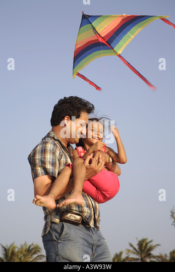 Father and daughter having fun on picnic flying a kite on beach enjoying sun sand and sea - Stock-Bilder