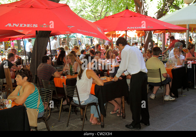 Argentina Mendoza Paseo Sarmiento pedestrian mall dining drinking sidewalk cafe alfresco umbrella table Hispanic - Stock Image