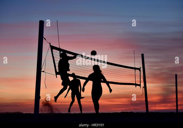 Silhouettes of female volleyball players practicing volleyball on a beach at sunset in Mission Beach, San Diego, - Stock-Bilder
