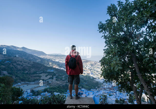 Tourist observing a panoramic view of blue city of Chefchaouen from fortified wall door, Morocco - Stock Image